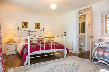 The master bedroom has a beautiful king size bedstead