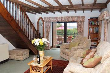 The spacious sitting-room with stairs leading up to the bedrooms.