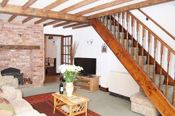 The stairs lead up from the living-room, where there is a feature fireplace with original brickwork.