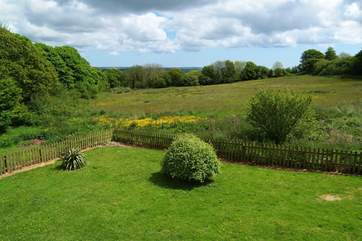 The view from the open plan living-room over the garden and meadows.