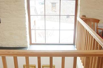 A large window above the stairwell allows light to flood into the property.