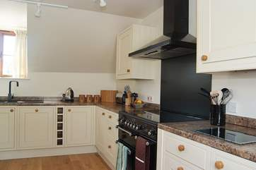 The kitchen has a contemporary black Rangemaster cooker.