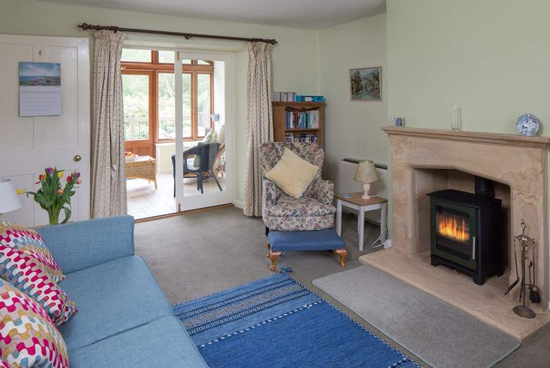 The open plan sitting/dining-room has a beautiful hamstone fireplace, cosy wood-burner and the garden-room beyond.