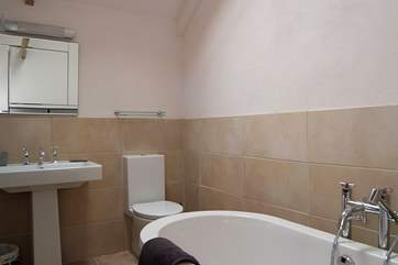 The beautifully tiled en suite has a contemporary free-standing bath.