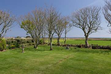 The view beyond the garden to the sea is uninterrupted apart from the trees.