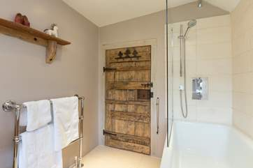There is a contemporary family bathroom with a bath and fitted shower. The historic door balances perfectly with the sparkling white fittings.
