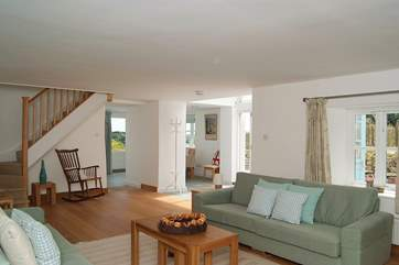 The open plan living-room has full height folding glass doors opening out to the garden.