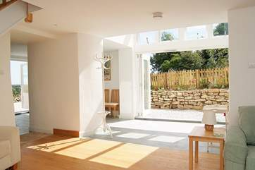 Light floods into the house through the double height folding glass doors.