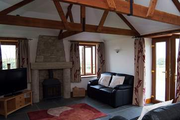 The sitting-area has a welcoming wood-burner and double doors leading outside to the patio and garden.
