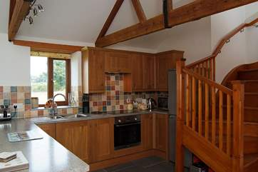 From the well-equipped kitchen a turning wooden staircase leads up to the first floor.