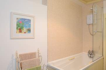 In the bathroom there is a step up to the bath which is fitted with an electric shower.