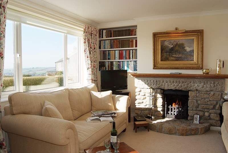 The sitting-room is beautifully furnished and has a lovely open fire.