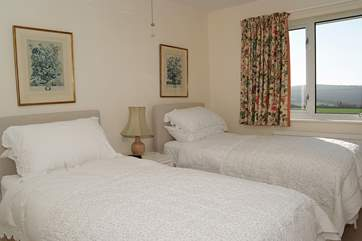 The twin bedroom with beautiful crisp white bed linen has views out across the surrounding countryside.