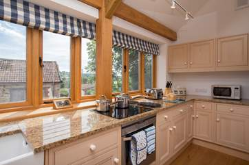 Cooking up a treat in this extremely well-equipped kitchen with a view across the back of the original farmstead is a treat too.