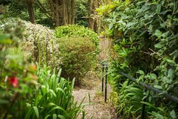 Take the steps and follow the path down through the terraced garden to the gate at the bottom for a shortcut to the cove.