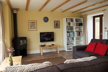 The cosy sitting-area with wood-burner, great television and books!