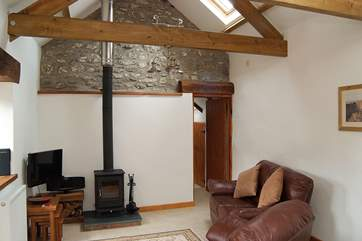 The cottage features a cosy wood-burner and a high open beamed ceiling, with part of the original stonework left exposed.