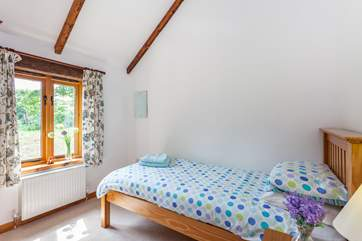 The cute second bedroom is suitable for an adult or child.