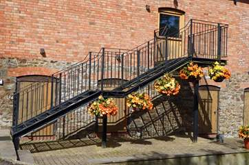 The steps are adorned with beautiful hanging baskets - there is some lovely planting around the little pond too.