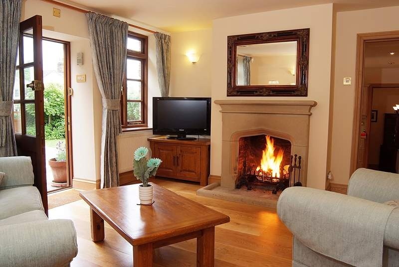 The sitting-room has solid wood floors and a traditional stone fireplace.