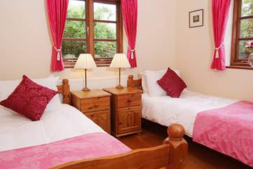 The twin bedroom (Bedroom 1) has windows on two sides, overlooking the garden.
