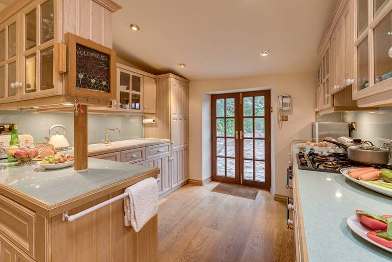 The kitchen is equipped as a home from home and has French windows to the stone terrace and garden.