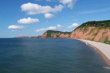 The view to the west from the clifftops at Sidmouth - a pebble beach with sand at low tide.