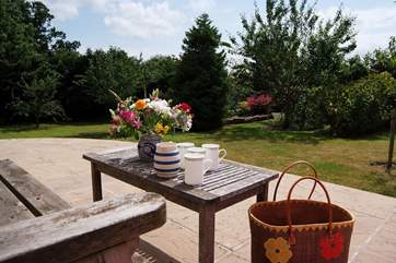 The sunny patio overlooks the beautiful garden and the panoramic views beyond it.