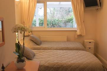 The pretty twin bedroom (Bedroom 2) has a wall-mounted television and overlooks the garden.