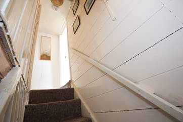 Steep cottage stairs lead up to the bathroom and the bedrooms.