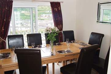 The dining-room table is set in front of the patio doors, making the most of the fabulous views towards the beach.