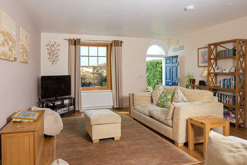 The spacious sea facing living-room in this lovely holiday home opens out onto the enclosed garden.