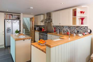 The kitchen is separated from the dining-area with  its clever and functional design.