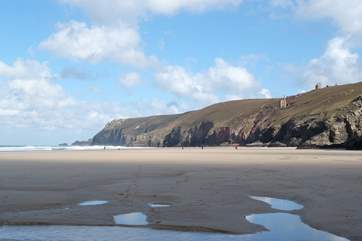 Nearby Chapel Porth beach at low tide with iconic mine buildings perched on the cliffs above.