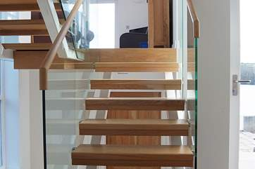 A half-flight of glass-sided, open-tread stairs leads from the entrance hall to the sitting-room.