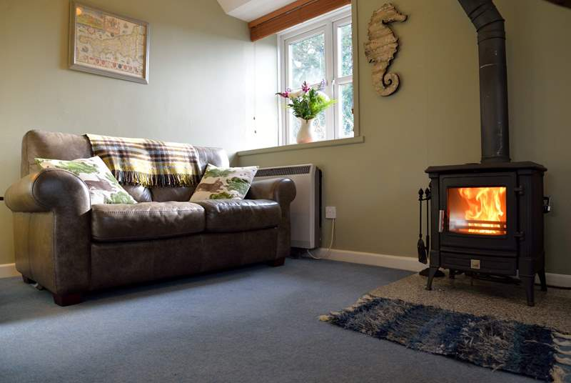 A comfortable sofa is set beside the wood-burner.