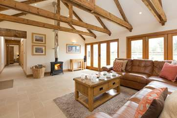 There is a high ceiling open plan living space with wonderful bi-fold doors that open up the side of the barn to the garden.
