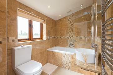 The ensuite bathroom is beautifully designed with a spa bath as well as the shower.