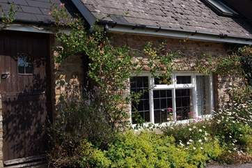 The friendly exterior of the cottage with its climbing roses.