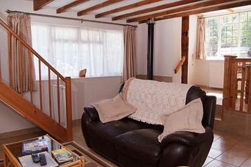 There is a cheerful open plan living area in this cottage. The dining-area is in the raised-area beyond.