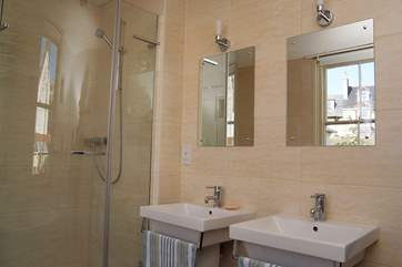 The bathroom has a double shower cubicle, a bath and his and her sinks.