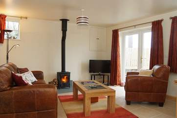 Wheel Barn has a comfortable open plan living-room with a wood-burner and French doors out to an enclosed garden.