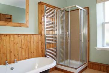 The bathroom has a shower cubicle as well as a roll-top bath.