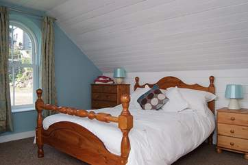 Spacious Bedroom 2, on the left at the top of the stairs, is furnished with a double bed.