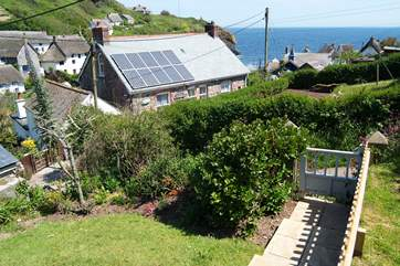 Steps from the patio descend to the little garden gate which opens onto the footpath leading down to the cove.