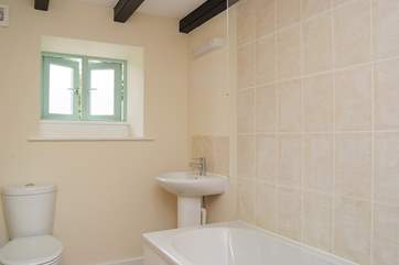 Bathroom with bath and fitted shower.