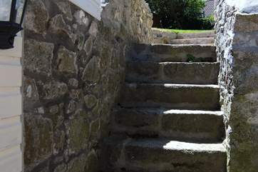 From the parking-area a flight of stone steps leads from outside the back door up to the back garden.