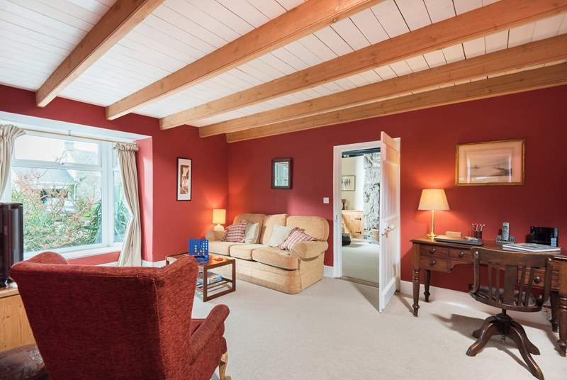 The unexpectedly spacious sitting-room at the centre of the cottage has the kitchen on one side and the cosy snug on the other.