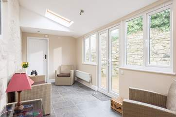 The sun-room links the ground floor shower-room and the rest of the cottage and gives access to the garden.
