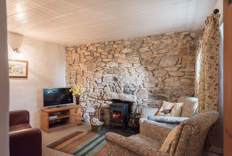 The cosy sitting-room is furnished with two comfy armchairs and a sofa around the wood-burner.